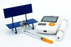 Miniature people: Businessman sitting on chair with glucose meter, syringe. Image use for health care concept.  Stock Photo