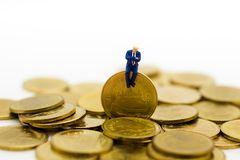 Miniature people: Businessman sitting on the coins with graph on wall. Image use for business competition concept.  Stock Image