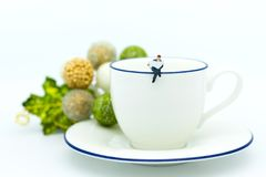 Miniature people : Businessman sitting on cup of coffee and have reading news paper. Image use for business concept Stock Photography
