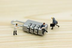 Miniature people:  Businessman sitting on master key encoding. Image use for background security system, hack, business concept.  Stock Images