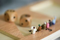 Miniature people : Businessman sitting with Rolling  two dice . Miniature people : Businessman sitting with Rolling  two dice Royalty Free Stock Photos