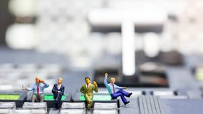 Miniature people : businessman sitting on switcher control of Te Stock Photos