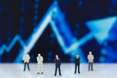 Miniature people: Businessman stand front of dashboard, display graphs, profit margins of  background. Image use for business Royalty Free Stock Image