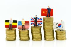 Miniature people: Businessman stand on stack coins with country flag , show the profits of marketing in each country. Image use for business concept Stock Photography