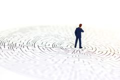 Miniature people: Businessman standing on center of maze. Concep Stock Photos