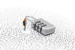 Miniature people: Businessman standing on center of maze with ke royalty free stock image