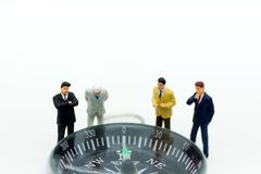 Miniature people :Businessman standing with compass. Image use for direction of the economy, investment for long-term profit.  Royalty Free Stock Photos