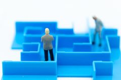 Miniature people: Businessman standing with maze. Image use for finding solution for solve problem, business concept.  Stock Photography
