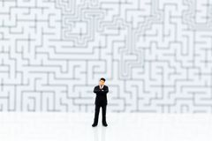 Miniature people: Businessman standing with a maze to background. Image use for find solution, business concept stock images