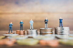 Miniature people businessman standing on money Royalty Free Stock Images