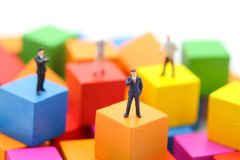 Miniature people : businessman standing on wood color block, using as background , business concept royalty free stock photo