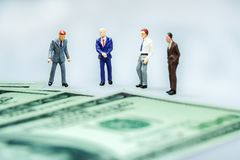 Businessman with US dollar bills. Miniature people : Businessman with US dollar bills. Business concept Stock Image