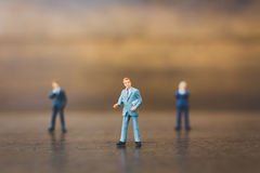 Miniature people businessman on wooden background Royalty Free Stock Image