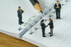 Miniature people with businessmen handshaking and others clapping on white note and pencil as business agreement concept royalty free stock images