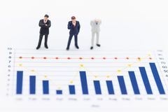 Miniature people : Businessmen looking benefit of work from the graph progress. Use as a business concept.  Royalty Free Stock Photography