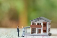 Miniature 2 people businessmen Shake hands with A model house model .as background business concept and real estate concept. With copy space stock photography