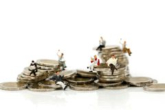 Miniature people: businessmen sitting on coins and reading news royalty free stock images