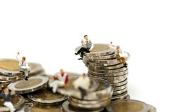 Miniature people: businessmen sitting on coins and reading news royalty free stock photo