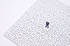 Miniature people businessmen standing in the center of the maze. Business Idea Concepts Troubleshooting Analysis of problems to. Find solutions royalty free stock photo