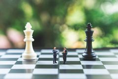 Miniature people businessmen standing on a chessboard with a chess piece on the back Negotiating in business. as background. Business concept and strategy stock images