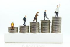 Miniature people : Businessmen standing on a coin stacked increase up respectively, used as a business concept.  Royalty Free Stock Image