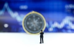 Miniature people : businessmen standing on a graph chart financ stock photo
