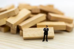 Miniature people : Businessmen standing in various positions of wooden , indicating the sequence of work, used as a business. Concept royalty free stock photos