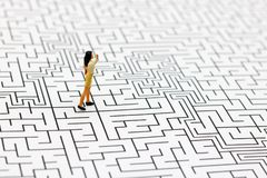 Miniature people: Businesswoman standing on center of maze. Concepts of finding a solution, problem solving and challenge. stock images