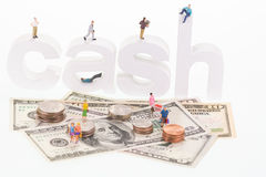 Miniature people on cash wooden letters and US banknotes. Miniature people sitting and standing on cash wooden letters and US banknotes Stock Photos