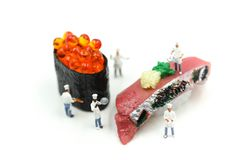 Miniature people : Chef with Salmon egg on sushi nigiri roll on. White background Stock Photo