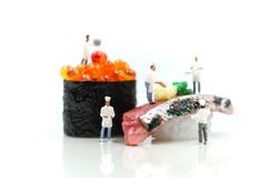 Miniature people : Chef with Salmon egg on sushi nigiri roll on. White background Stock Photos