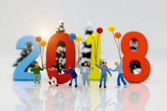 Miniature people, children with colorful balloons standing in front of number 2018,. Family concept Royalty Free Stock Images