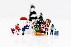 Miniature people: children enjoy with Santa Claus and snowman. Christmas day concept stock photography
