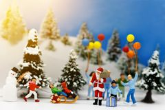 Miniature people: children enjoy wiht Santa Claus and snowman. Christmas day concept royalty free stock photography