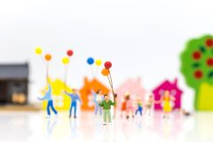Miniature people: children hold balloons, and play together, using as background International day of families concept. Miniature people: children hold balloons stock photography