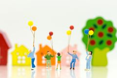 Miniature people: children hold balloons, and play together, using as background International day of families concept. Miniature people: children hold balloons royalty free stock images