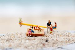 Miniature people: Children play on the swings on the beach with. Mother. Concept of happy family day Royalty Free Stock Photo