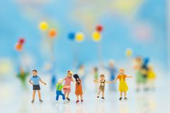 Miniature people: Children play together fun. Backdrop is a map of the world, using as background International day of families concept Stock Photo