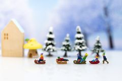 Miniature people: Children playing on snow funny together. Image use for Christmas festival. Miniature people: Children playing on snow funny together. Image royalty free stock photo