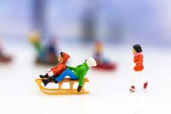 Miniature people: Children playing on snow funny together. Image use for Christmas festival. Miniature people: Children playing on snow funny together. Image royalty free stock photos