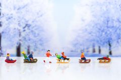 Miniature people: Children playing on snow funny together. Image use for Christmas festival. Miniature people: Children playing on snow funny together. Image stock photo