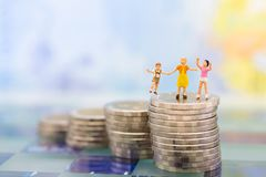 Miniature people: Children standing on top of stack coins . Image use for background , Life insurance concept.  Stock Photography