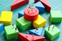 Miniature people : children with wooden block and mini toy horse. Education concept Royalty Free Stock Images