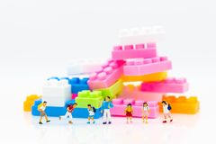 Miniature people: Childrens with colorful puzzle piece. Image use for child`s toy, education concept.  Stock Photos