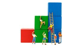 Miniature people: Climber looking up while challenging route. On growth graph with wood ladder, Concept of the path to purpose and success Stock Image