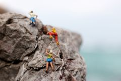 Miniature people: Climber looking up while climbing challenging. Route on cliff, Concept of the path to purpose and success stock images
