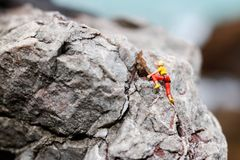 Miniature people: Climber looking up while climbing challenging Stock Photography