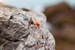 Miniature people: Climber looking up while climbing challenging Stock Photo
