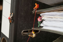 Miniature people climbing binders. Miniature people group of climbers ascending document binders Royalty Free Stock Image