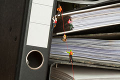 Miniature people climbing binders Stock Photo